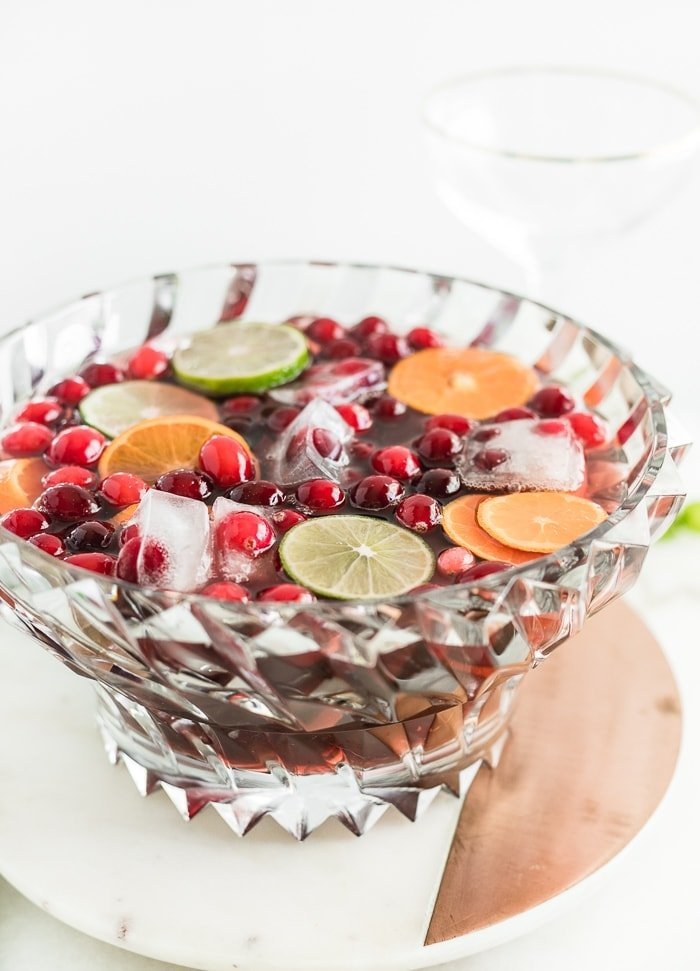 a punch bowl filled with Christmas punch on top of a white and copper round serving platter.
