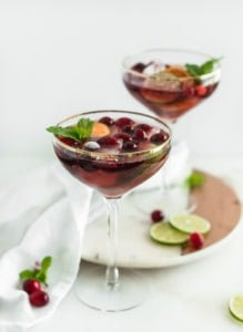 Two coupe glasses filled with red Christmas punch surrounded by sliced limes and cranberries.