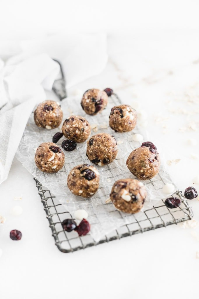 cranberry bliss balls on a rectangular cooling rack covered in parchment, surrounded by dried cranberries and white chocolate chips.