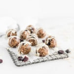 cranberry bliss balls drizzled with white chocolate on a rectangular cooling rack covered in parchment, surrounded by dried cranberries and white chocolate chips.