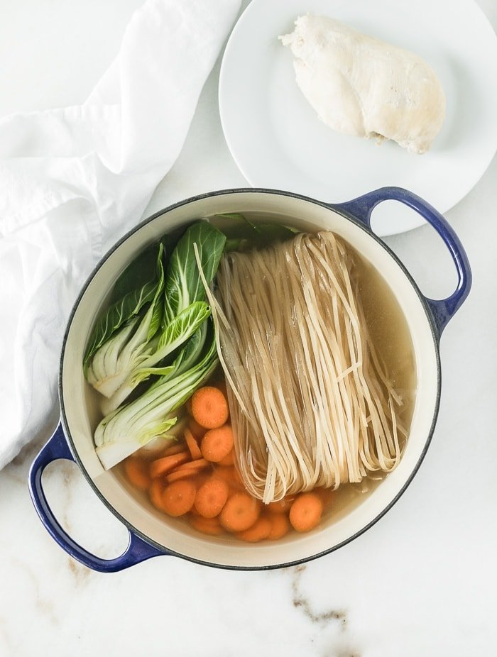 blue dutch oven with broth, bok choy, carrots, and brown rice noodles.