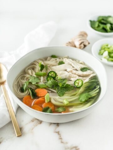ginger lemongrass chicken noodle soup in a grey bowl, surrounded by a gold spoon, ginger, and fresh herbs.