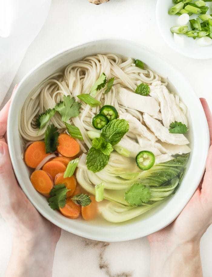 two hands holding a bowl of ginger lemongrass chicken noodle soup.