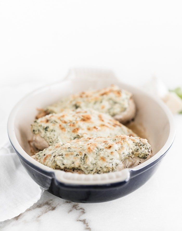 three baked spinach artichoke chicken breasts in a blue oval baking dish.