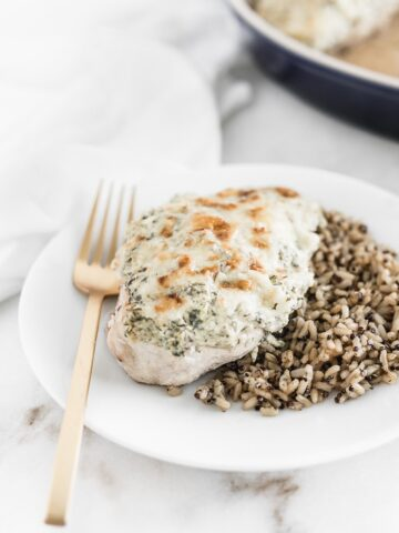 baked spinach artichoke chicken breast on a white plate with rice and a gold fork.