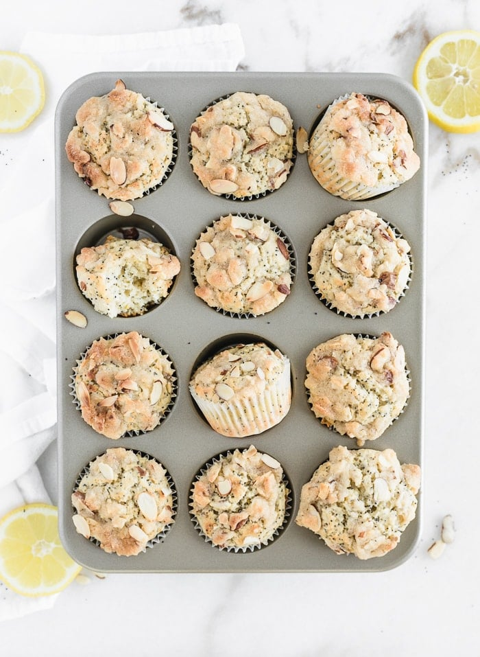 overhead view of lemon poppy seed muffins in a muffin tin surrounded by sliced lemons.