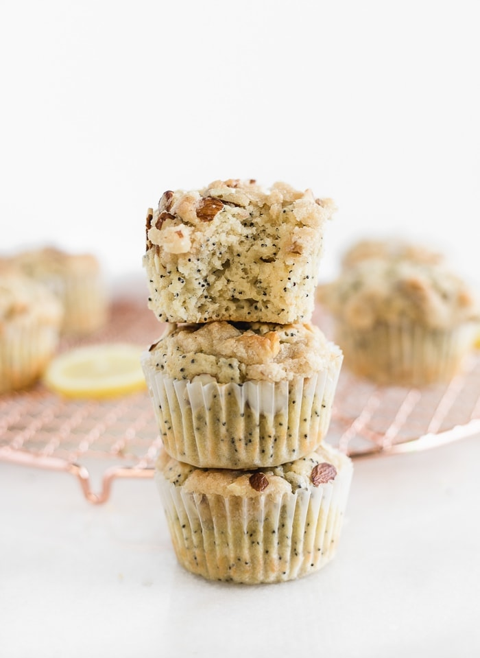 three lemon poppy seed muffins stacked on top of each other. The top one has a bite taken out of it.