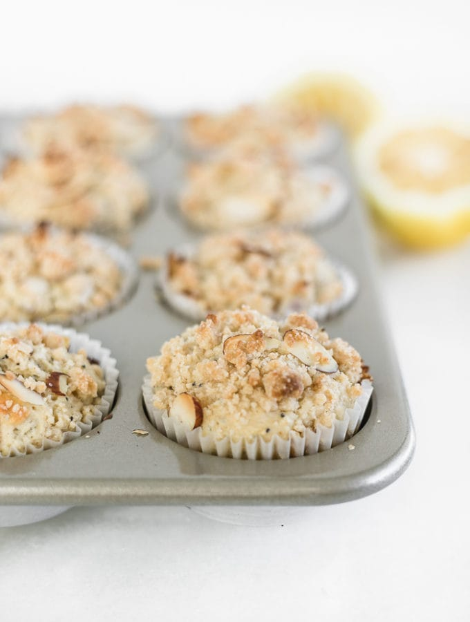 lemon poppyseed muffins with streusel topping in a muffin tin.