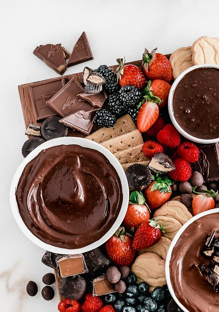 overhead view of berries, chocolates, and chocolate spreads on a brown wooden board.