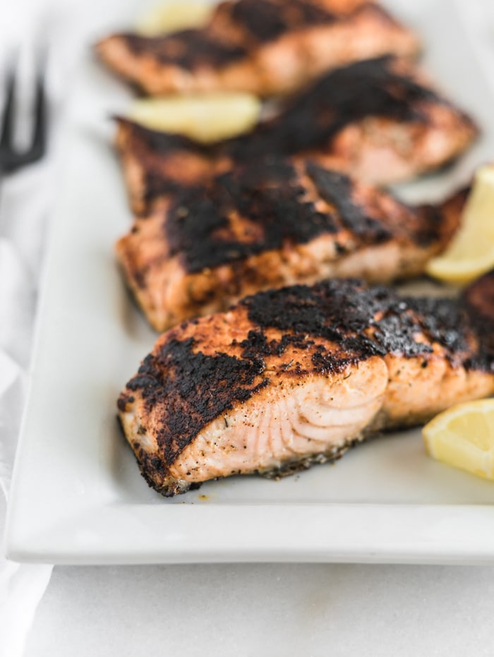 blackened salmon filets on a white rectangular platter with lemon wedges.