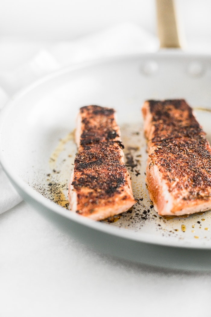 salmon filets in a nonstick white skillet.