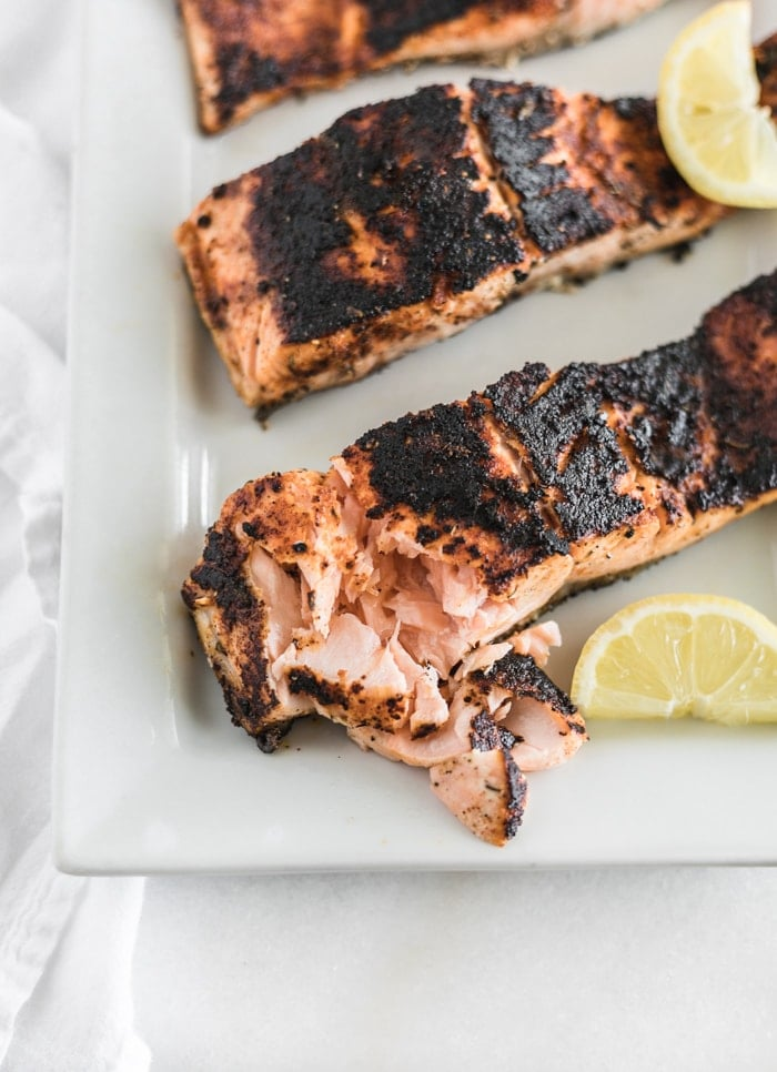 a filet of blackened salmon with flakes removed on a white platter with lemon wedges.