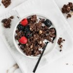 overhead shot of chocolate hazelnut granola in a bowl with milk and berries with a black spoon on top of a white and grey napkin.