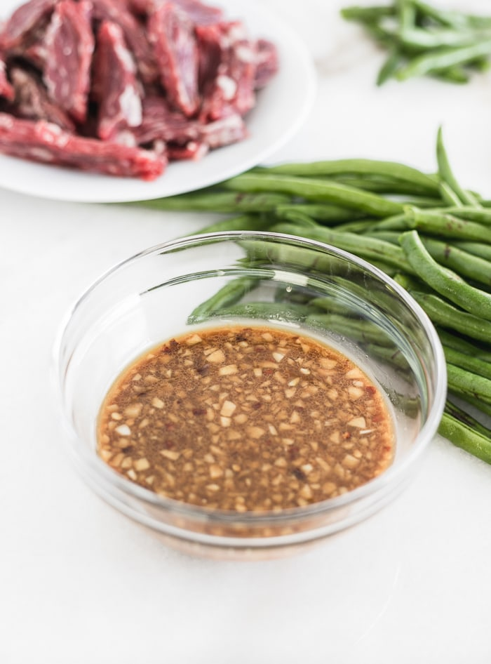 sesame ginger stir fry sauce in a glass bowl with green beans and sliced beef behind it.