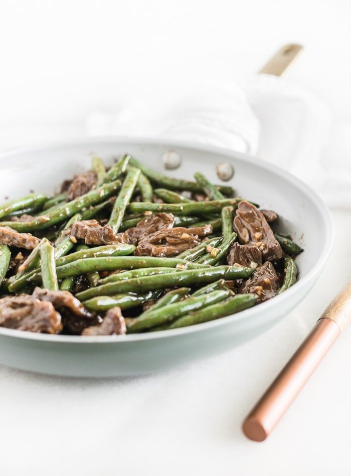 sesmae ginger beef and green beans in a skillet.