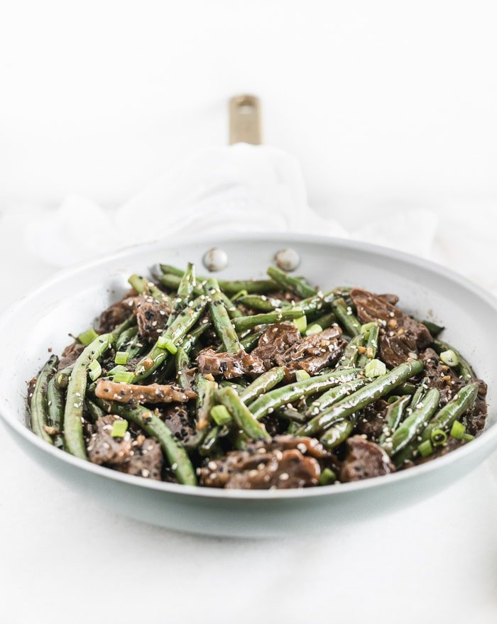 sesame ginger beef and green beans in a skillet.