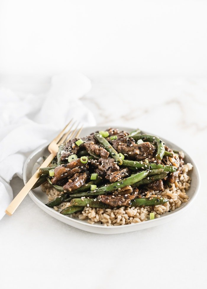 sesame ginger beef and green beans on top of brown rice on a white plate with a gold fork.
