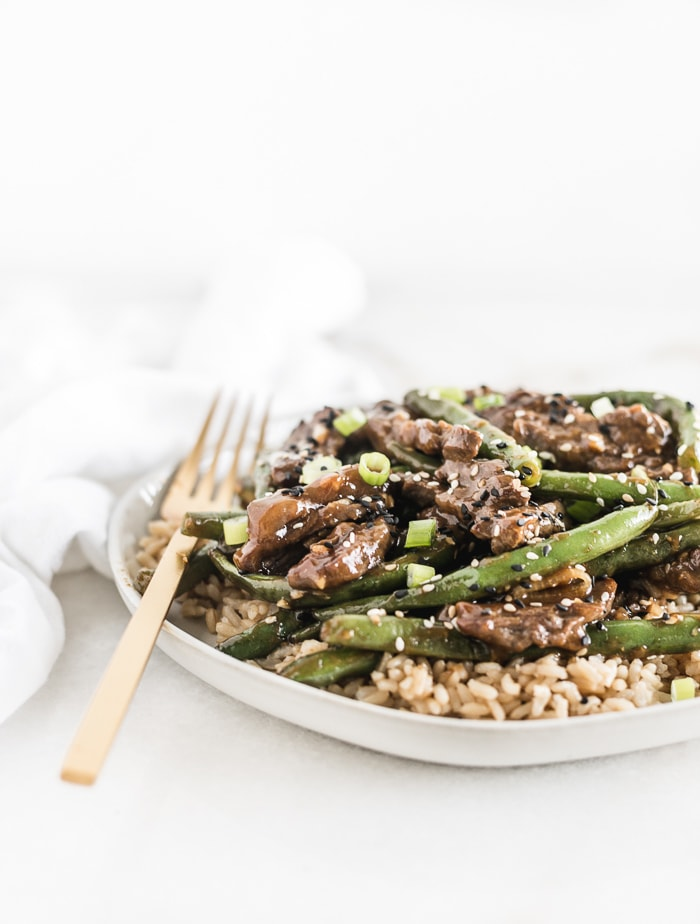 Sesame ginger beef and green beans over brown rice on a white plate with a gold fork.