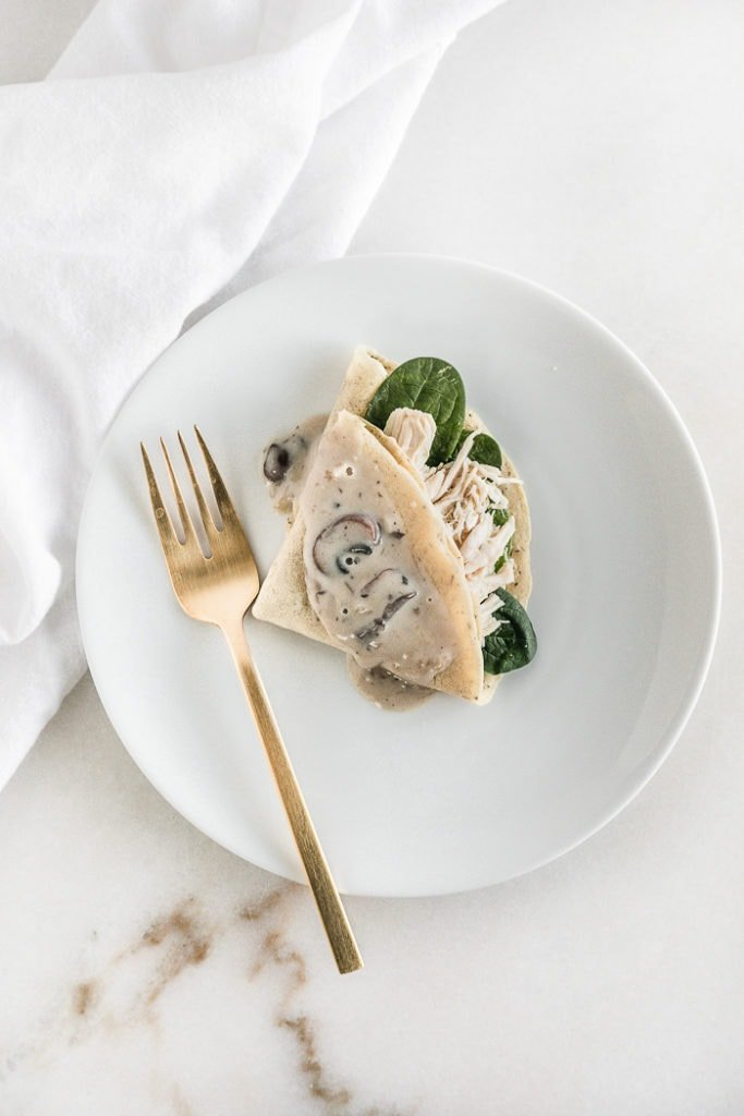 overhead view of a crepe stuffed with chicken topped with mushroom sauce on a white plate with a gold fork.