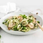 zucchini noodles with shrimp, peas and mint pesto on a white plate with a gold fork.