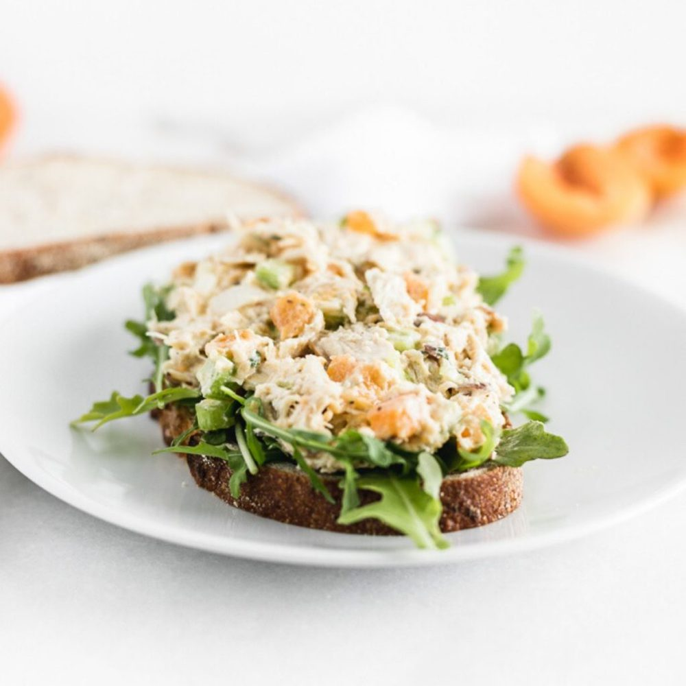 apricot chicken salad on top of arugula on a slice of bread.