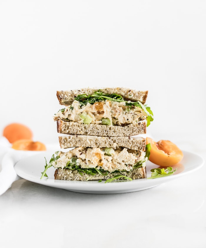 apricot chicken salad sandwich halves stacked on top of each other on a white plate.