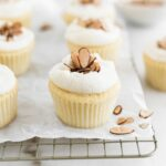 burnt almond cupcake on a cooling rack with more cupcakes in the background.
