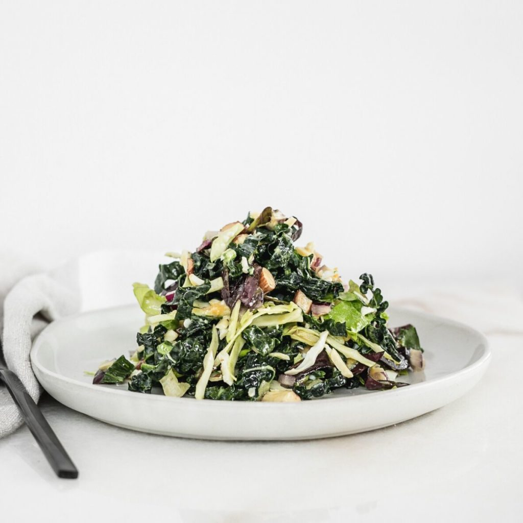 kale salad piled on top of a white plate.