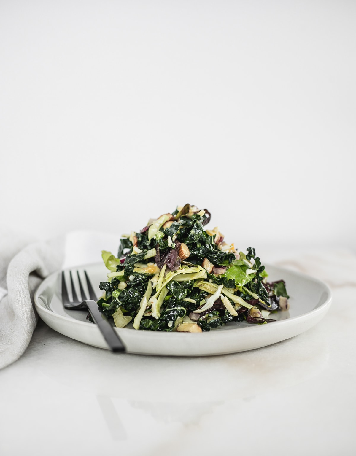 kale salad piled on top of a white plate with a black fork.