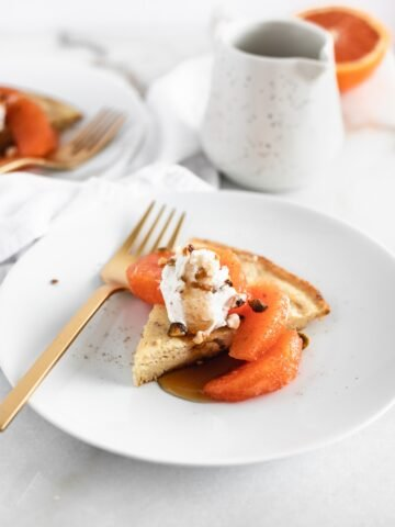 slice of skillet pancake topped with cara cara oranges and whipped cream on a white plate with a gold fork.