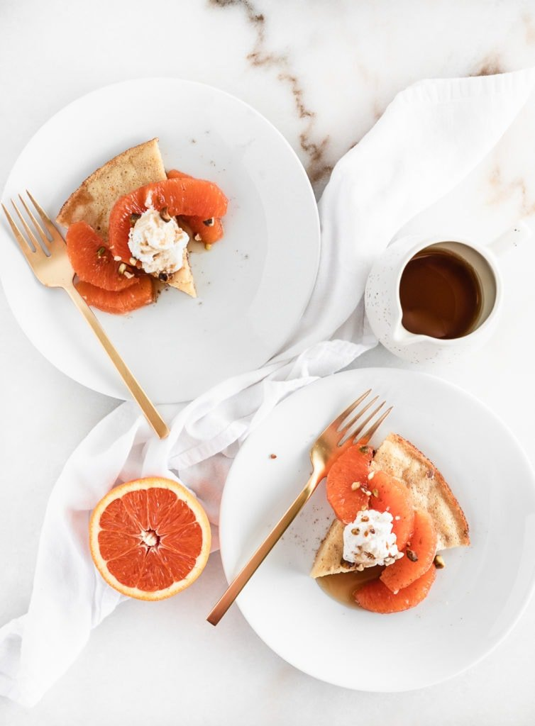 overhead view of two white plates with slices of skillet pancakes topped with cara cara oranges and whipped cream.