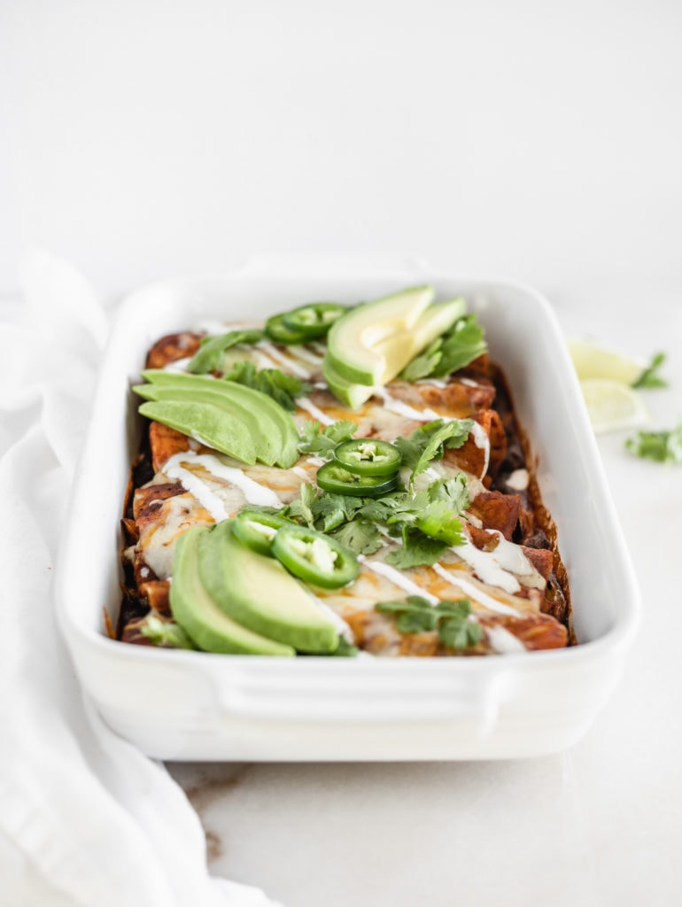 sweet potato black bean enchiladas with red sauce in a white baking dish topped with avocado, cilantro, jalapeno, and sour cream.