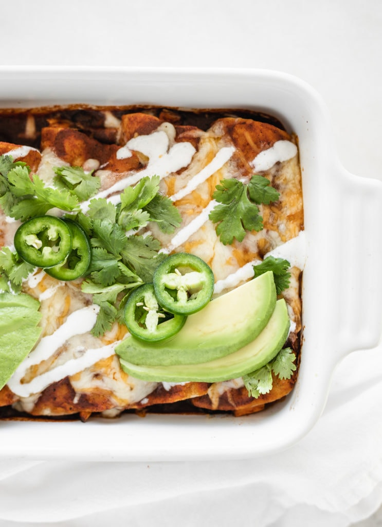 overhead view of sweet potato black bean enchiladas with red sauce in a white baking dish topped with avocado, cilantro, jalapeno, and sour cream.