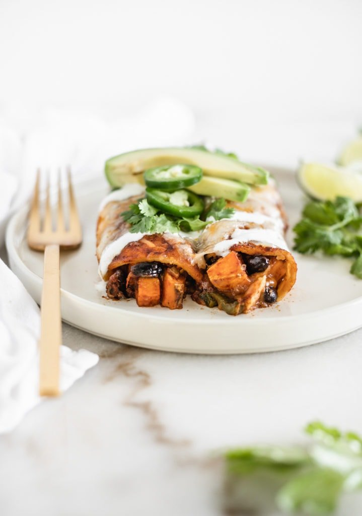 two sweet potato black bean enchiladas on a white plate topped with avocado and jalapeno slices.