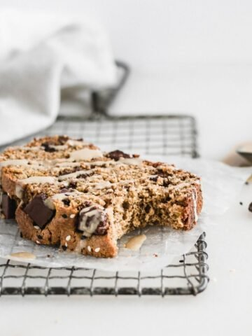 slice of tahini chocolate chip banana bread on a metal cooling rack drizzled with tahini.