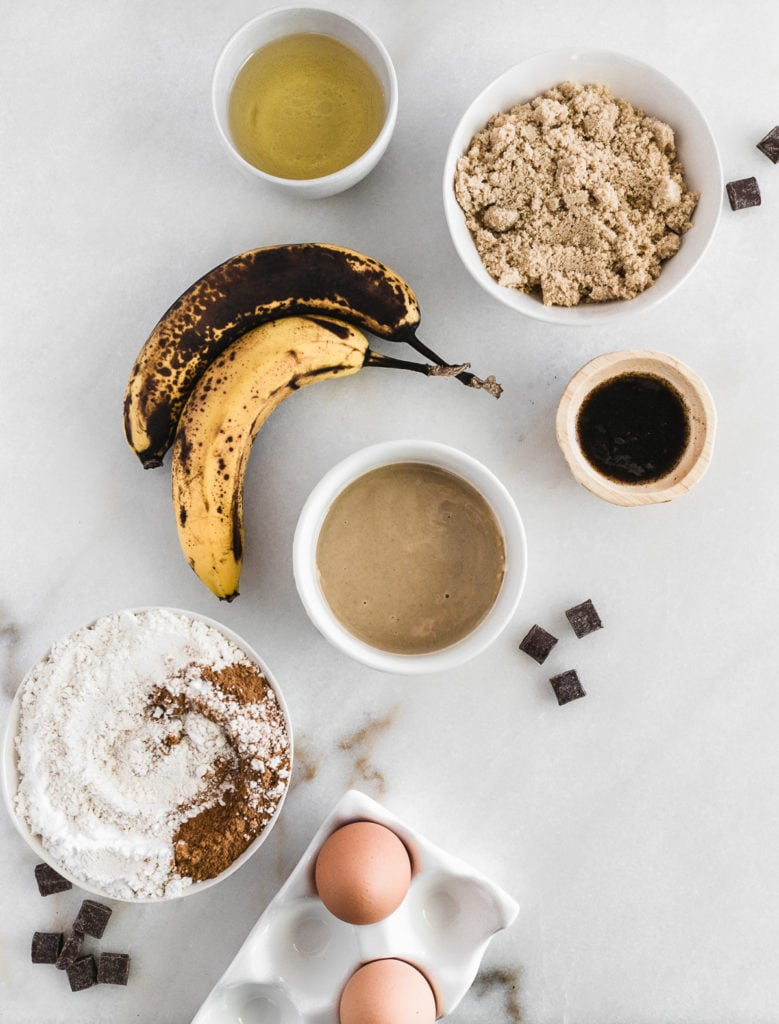 Overhead view of ingredients for tahini banana bread on a white background.
