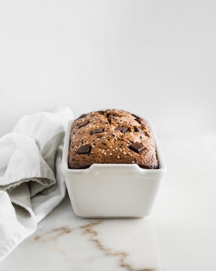 tahini chocolate chip banana bread in a white loaf pan.