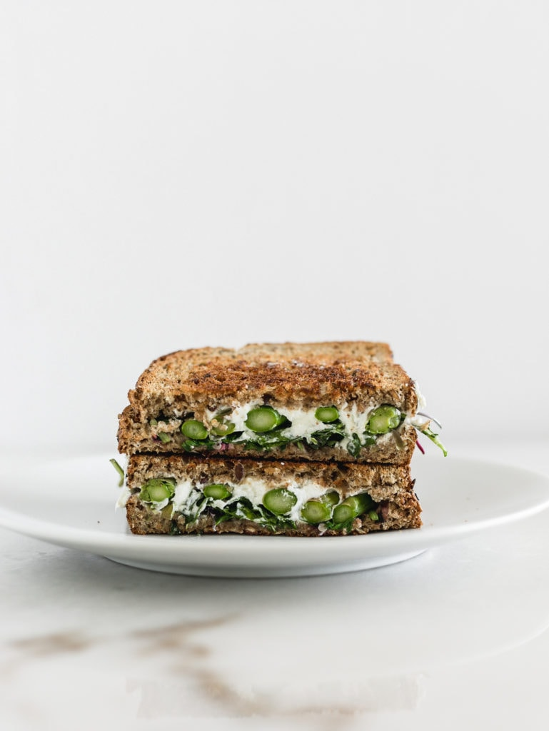 asparagus and goat cheese grilled cheese sandwich cut in half and stacked on a white plate.
