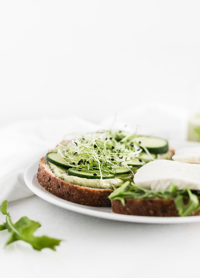 open faced green goddess sandwich on a white plate.