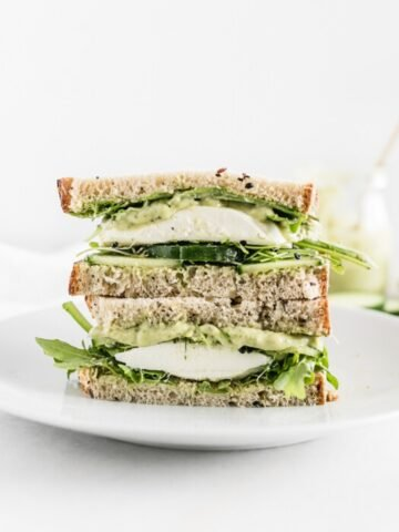 green goddess sandwich with mozzarella cut in half and stacked on a white plate.