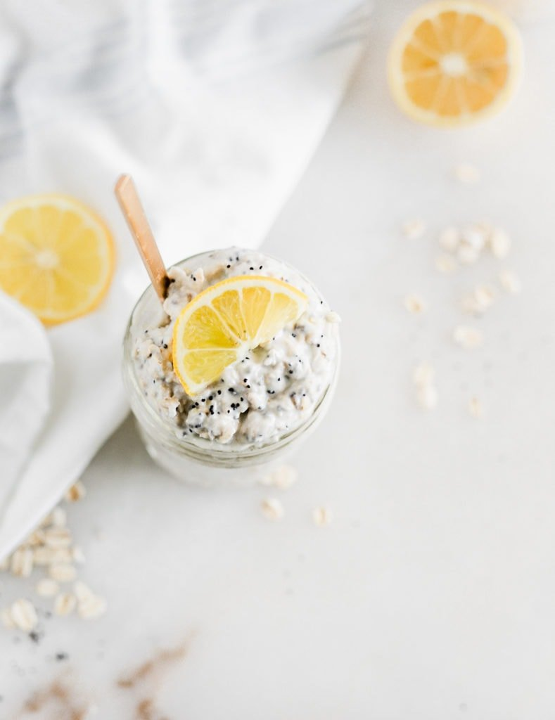 overhead view of a jar of lemon poppy seed overnight oats with a lemon slice on top.