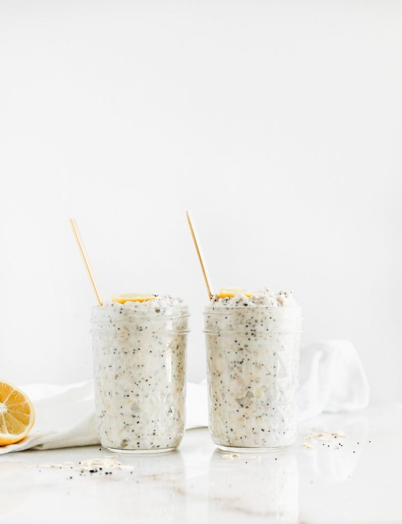 two jars of lemon poppy seed overnight oats with gold spoons in them.