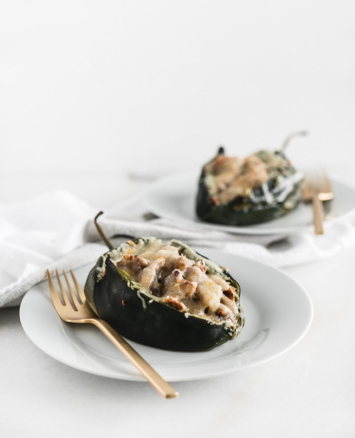 pulled pork stuffed poblano peppers covered with cheese on white plates with gold forks.