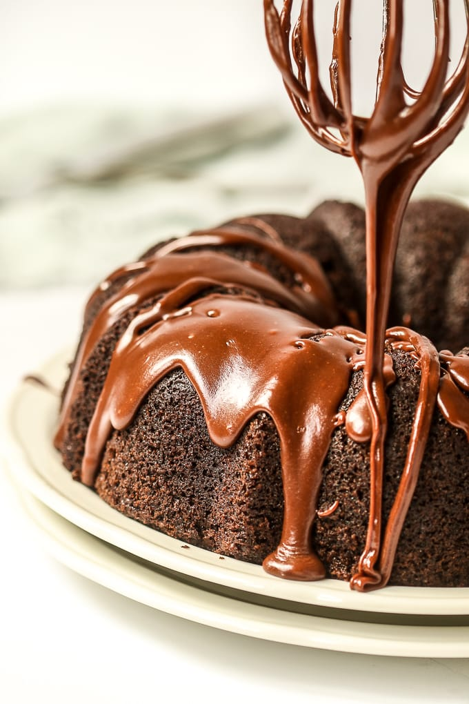 closeup of sourdough chocolate bundt cake with icing being drizzled over it.