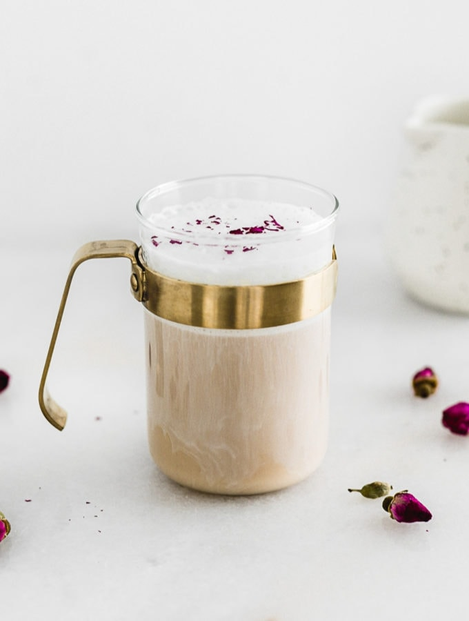 cardamom rose latte in a glass mug with a gold handle surrounded by rose buds.