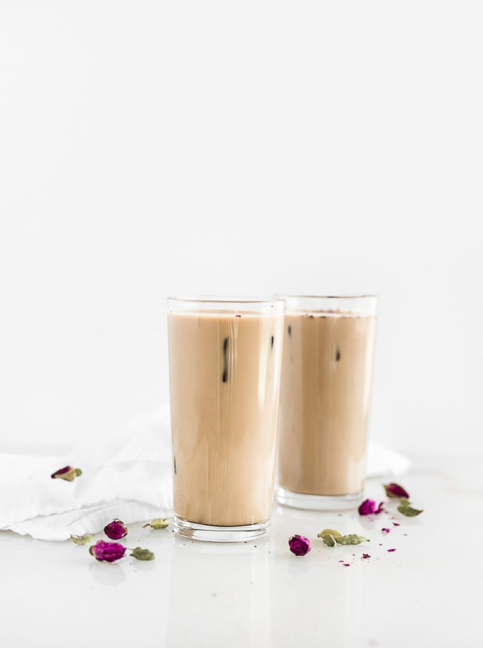 two iced cardamom rose lattes in glasses surrounded by rose buds and cardamom pods.