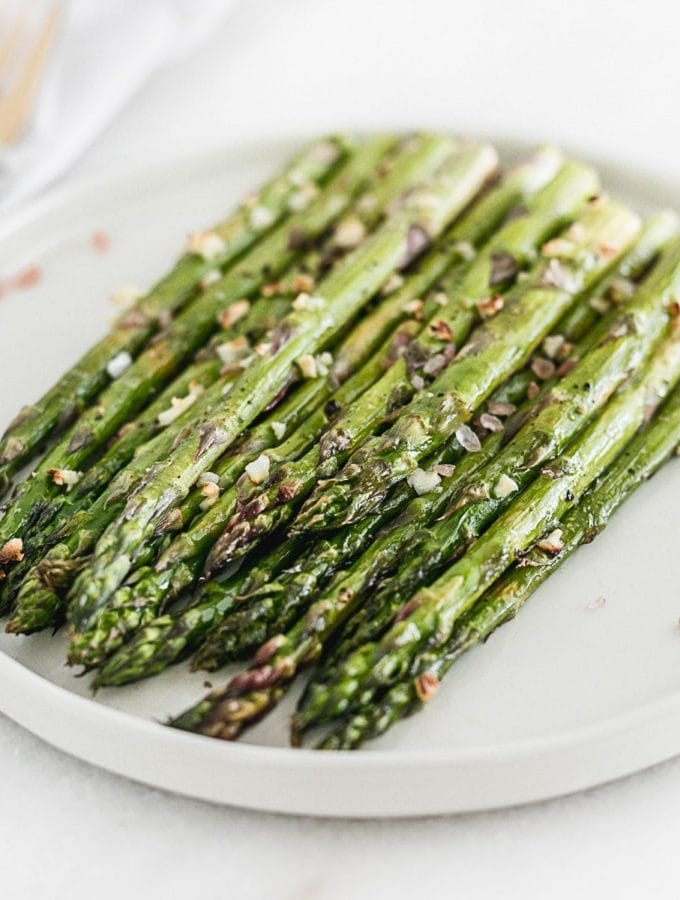 broiled asparagus on a white plate.