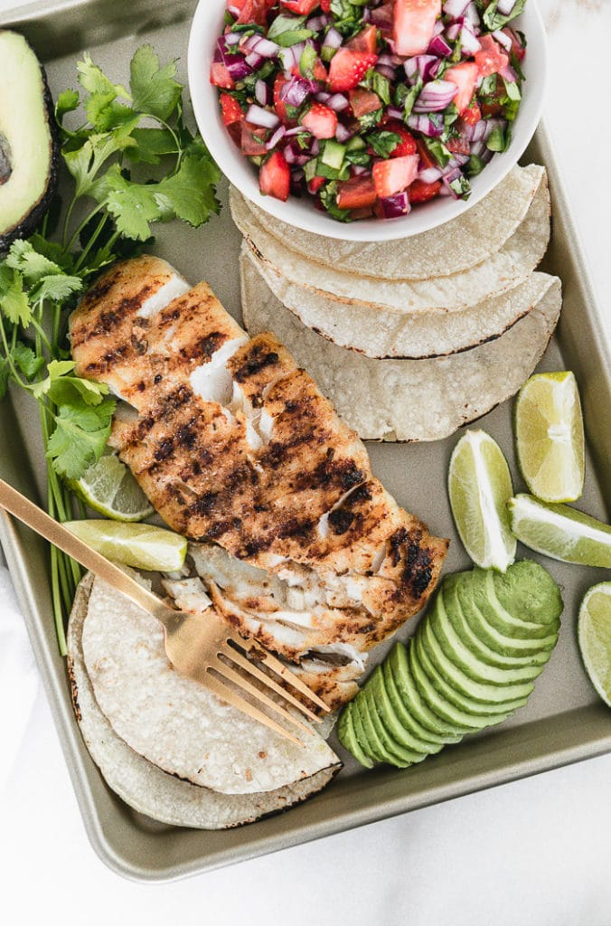 grilled fish on a n a baking sheet with a bowl of strawberry salsa, tortillas, sliced avocado, limes and cilantro.