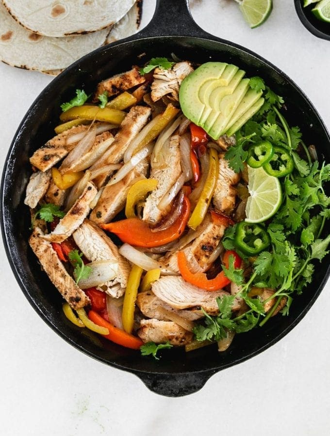 overhead view of chicken fajitas with peppers and onions in a skillet.