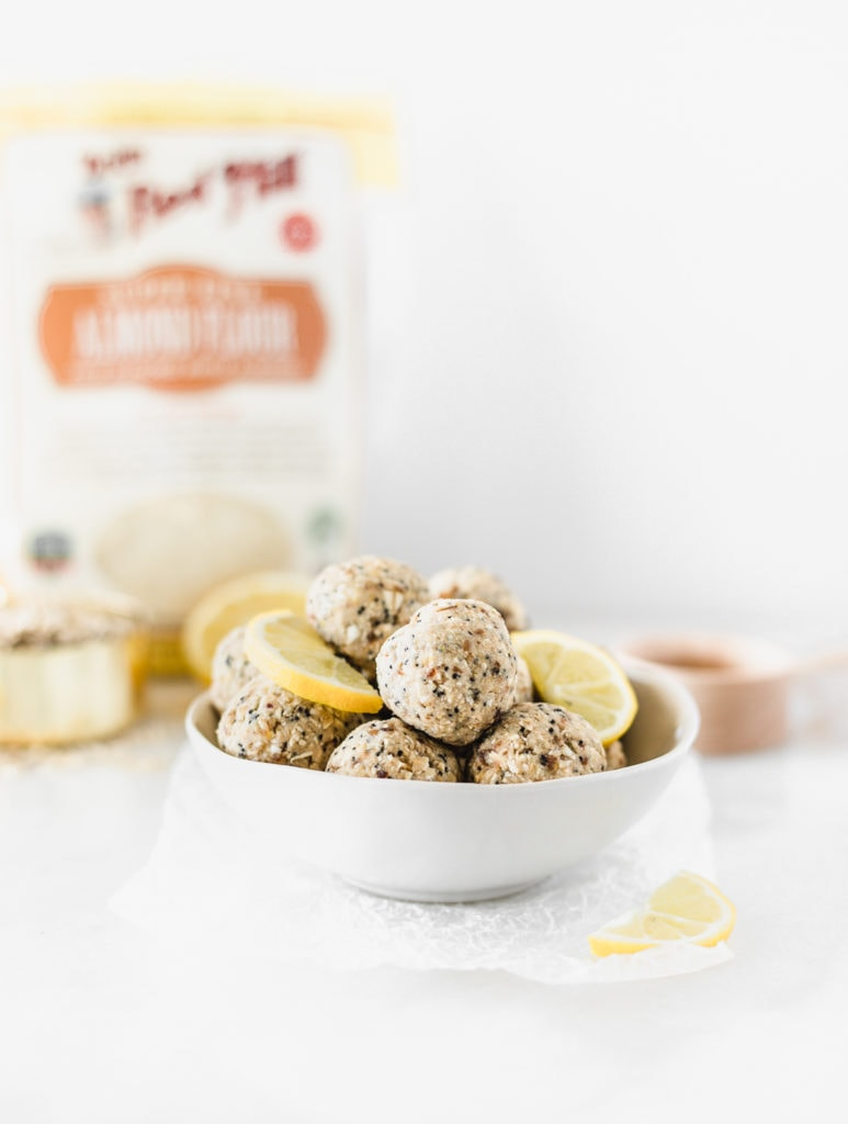 lemon poppy seed balls in a white bowl with lemon slices, with almond flour and a measuring cup in the background.